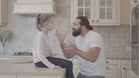 Uomo barbuto che racconta emozionalmente storia alla sua piccola figlia, attivamente gesticolante nella cucina La ragazza si sied archivi video