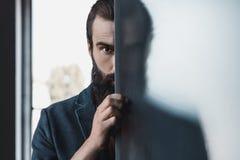 Uomo barbuto che si nasconde dal vetro glassato fotografia stock