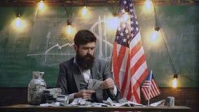 Uomo barbuto con i soldi del dollaro per il dono Riforma americana di istruzione alla scuola nel 4 luglio Festa dell'indipendenza video d archivio