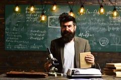 Uomo barbuto con il libro e la retro macchina da scrivere Lo scienziato fa la ricerca con il microscopio Uomo con la barba ed i b Immagine Stock