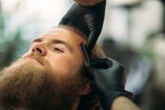 Uomo barbuto con la barba lunga che ottiene capelli alla moda che si radono, taglio di capelli, con il rasoio dal barbiere in par fotografia stock libera da diritti