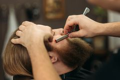 Uomo barbuto con la barba lunga che ottiene capelli alla moda che si radono, taglio di capelli, con il rasoio dal barbiere in par immagine stock