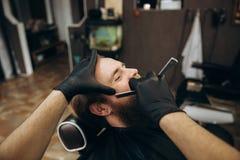 Uomo barbuto con la barba lunga che ottiene capelli alla moda che si radono, taglio di capelli, con il rasoio dal barbiere in par fotografie stock libere da diritti