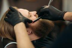 Uomo barbuto con la barba lunga che ottiene capelli alla moda che si radono, taglio di capelli, con il rasoio dal barbiere in par immagini stock