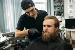Uomo barbuto con la barba lunga che ottiene capelli alla moda che si radono, taglio di capelli, con il rasoio dal barbiere in par immagini stock libere da diritti