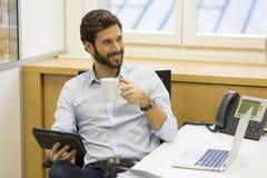 Uomo barbuto dei pantaloni a vita bassa bei che lavora nell'ufficio sul computer Fotografia Stock