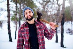 Uomo barbuto dei pantaloni a vita bassa in una foresta nevosa di inverno con l'ascia su una spalla Woodman che sta nell'ispezione immagine stock
