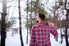 Uomo barbuto dei pantaloni a vita bassa in una foresta nevosa di inverno con l'ascia su una spalla Woodman che sta nell'ispezione fotografia stock
