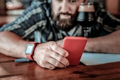 Uomo barbuto deludente che esamina il suo telefono rosso fotografia stock