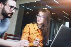 Uomo barbuto di affari e una ragazza in vetri ad una riunione che lavora ad un computer portatile Fotografia Stock Libera da Diritti