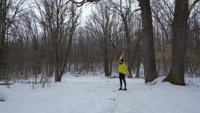 Uomo barbuto di sport in cappotto giallo che si scalda nella foresta di inverno con spazio libero video d archivio