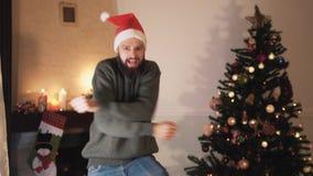 Uomo barbuto divertente che balla vicino all'albero di Natale L'uomo bello felice in cappello di Santa muove il suoi corpo e sorr video d archivio