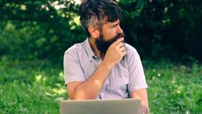 Uomo barbuto divertente che lavora con un computer portatile nel parco Freelance o il telelavoro, concetto di chiacchierata onlin archivi video