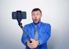 Uomo barbuto divertente in legame che fa selfie con un bastone Fotografie Stock Libere da Diritti