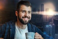 Uomo barbuto emozionale che sorride mentre bevendo tè Fotografia Stock