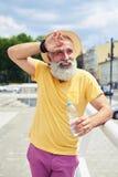 Uomo barbuto esaurito che sta con la bottiglia di plastica Fotografia Stock Libera da Diritti