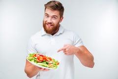 Uomo barbuto felice che indica dito al piatto con insalata fresca Immagini Stock
