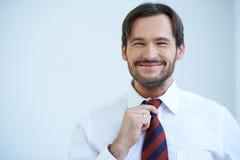 Uomo barbuto felice che raddrizza suo legame Immagine Stock