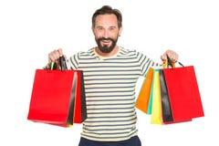 Uomo barbuto felice che sostiene i sacchetti della spesa variopinti Natale e concetto di feste uomo felice e sorriso che tiene lo Immagine Stock