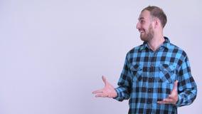 Uomo barbuto felice dei pantaloni a vita bassa che tocca qualcosa e che sembra sorpreso archivi video