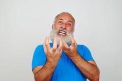 Uomo barbuto invecchiato che fa smorfie alla macchina fotografica che esprime nerv estremo immagine stock