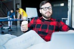 Uomo barbuto moderno che raffredda nell'ufficio fotografie stock