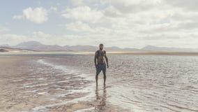 Uomo barbuto muscolare attraente che sta sulla riva di mare all'alba Ritratto laterale di giovane funzionamento barbuto sano dell Fotografie Stock