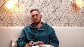 Uomo barbuto nel video gioco verde del gioco dell'accappatoio, nella vittoria ed in molto felice a questo proposito video d archivio