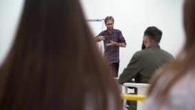 Uomo barbuto nelle conferenze di vetro ad una conferenza, parlante con le emozioni e gesticolare archivi video