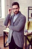 Uomo barbuto piacevole bello che tocca i suoi vetri fotografie stock