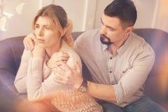Uomo barbuto piacevole che si siede con la sua moglie fotografia stock