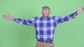 Uomo barbuto senior felice dei pantaloni a vita bassa che guarda intorno e che ritiene emozionante archivi video