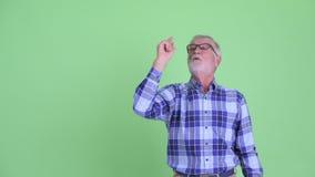 Uomo barbuto senior felice dei pantaloni a vita bassa che indica su e che sembra sorpreso video d archivio