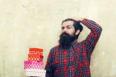 Uomo barbuto serio che giudica i contenitori di regalo variopinti impilati in mani Immagini Stock