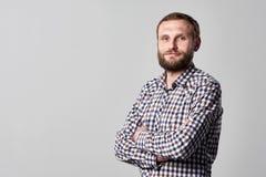 Uomo barbuto serio che sta con le mani piegate fotografia stock libera da diritti