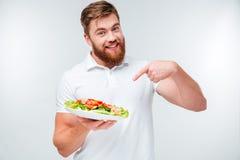 Uomo barbuto sorridente che indica dito al piatto con insalata fresca Immagine Stock Libera da Diritti
