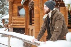 Uomo barbuto sorridente che sta vicino al cottage di legno nell'inverno Immagine Stock