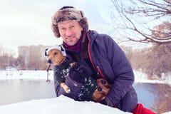 Uomo barbuto sorridente e piccolo cane in cappelli divertenti di inverno Immagini Stock