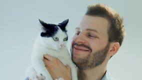 Uomo barbuto sorridente felice con il gatto domestico in bianco e nero, emozione umana archivi video