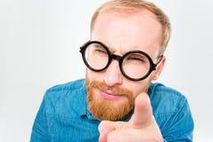 Uomo barbuto sospettoso in vetri rotondi divertenti che indica su voi Fotografie Stock Libere da Diritti