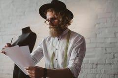 Uomo barbuto in strati della tenuta del cappello immagine stock libera da diritti