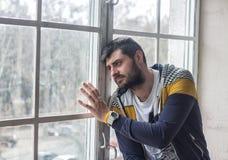 Uomo barbuto triste che guarda attraverso la finestra Immagine Stock