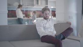 Uomo barbuto triste che si siede sullo strato in salone La donna ed il ragazzino sono nei precedenti Relazioni di famiglia stock footage