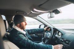 Uomo barbuto vestito caldo che conduce una nuova auto moderna Automobile interna v immagine stock libera da diritti