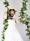 Uomo barbuto in vestito da sposa di una donna sul suo corpo nudo, aderente alla vite fare smorfie e divertente sulla sua testa a Fotografie Stock
