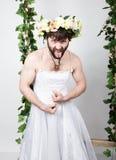 Uomo barbuto in vestito da sposa di una donna sul suo corpo nudo, facente smorfie e mostrante lingua Sulla sua testa una corona d Immagini Stock