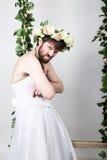 Uomo barbuto in vestito da sposa di una donna sul suo corpo nudo, piegato le sue armi, è scontentato sulla sua testa una corona d Immagini Stock