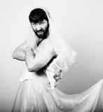 Uomo barbuto in vestito da sposa di una donna sul suo corpo nudo, tenente un fiore sposa barbuta divertente, in bianco e nero Fotografia Stock