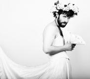 Uomo barbuto in vestito da sposa di una donna sul suo corpo nudo, tenente un fiore Sulla sua testa una corona dei fiori divertent Fotografia Stock