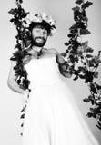 Uomo barbuto in vestito da sposa di una donna sul suo corpo nudo, tenente un fiore Sulla sua testa una corona dei fiori divertent Fotografia Stock Libera da Diritti
